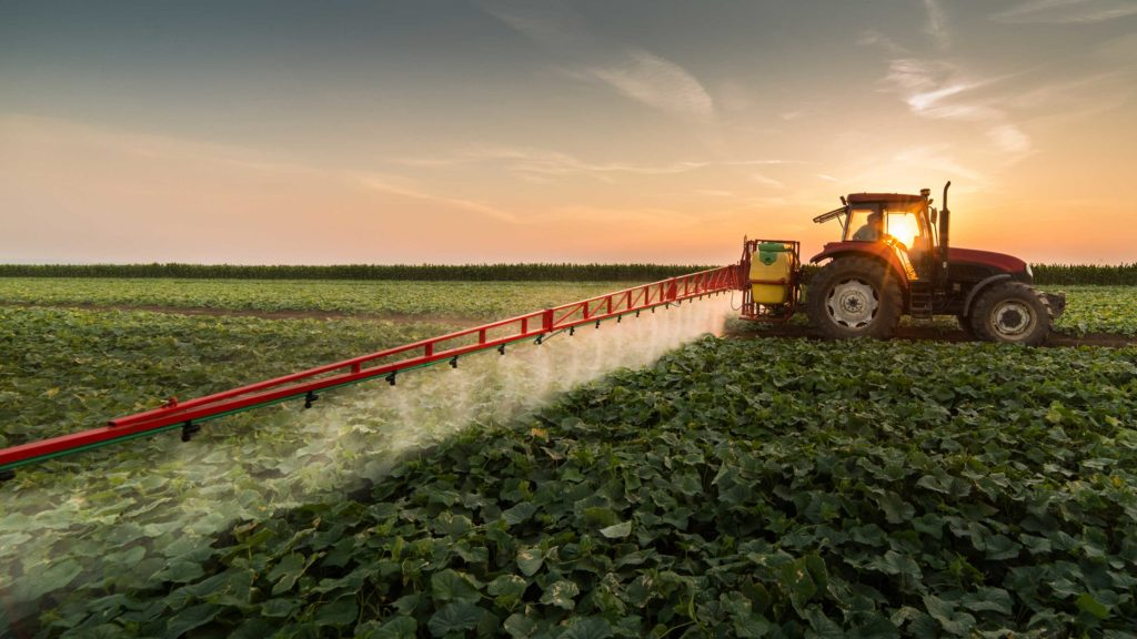 tractor in a field spraying crops